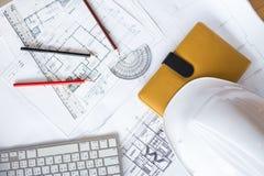 Imagem dos modelos com lápis e o capacete de segurança nivelados na tabela Imagens de Stock Royalty Free