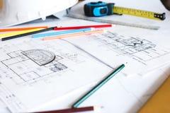 Imagem dos modelos com lápis e o capacete de segurança nivelados na tabela Imagem de Stock Royalty Free