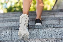 Imagem dos pés caucasianos da mulher do atleta que vestem as sapatilhas, indo acima fotografia de stock