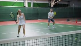 Imagem dos pares felizes que jogam o tênis na corte interna Os jovens vestidos no equipamento do esporte estão passando o tempo j filme