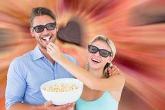 Imagem dos pares novos felizes que vestem os vidros 3d que comem a pipoca Fotografia de Stock Royalty Free