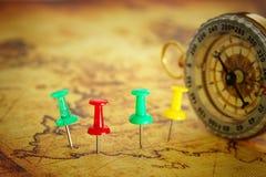 Imagem dos pinos unidos ao mapa, mostrando o destino do lugar ou do curso sobre o mapa velho ao lado do compasso do vintage Foco  imagem de stock royalty free