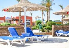 Imagem dos sunbeds e dos parasóis do bastão perto do poolzone em uma área do hotel imagem de stock royalty free