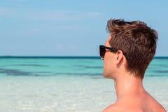 Imagem dos três quartos de um homem novo na praia que olha o mar azul claro fotos de stock royalty free