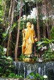 A imagem dourada de Buddha está estando em um arbusto Fotografia de Stock