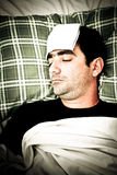 Imagem dramática de um homem doente na cama com febre Fotografia de Stock Royalty Free