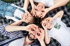 Imagem engraçada da família que faz círculos engraçados com seus dedos nos olhos Estão jogando Todo estão encontrando-se sobre Foto de Stock