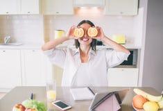 Imagem engraçada da morena que senta-se na tabela e que guarda partes de laranja na frente dos olhos A parte traseira pode consid foto de stock