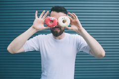 Imagem engraçada do homem que guarda dois anéis de espuma coloridos em torno de seus olhos Está olhando na câmera e no sorriso O  fotografia de stock royalty free