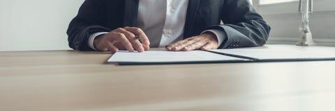 Imagem larga da vista do homem de negócios que senta-se em sua mesa de escritório com p fotografia de stock royalty free