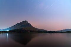 Imagem longa da exposição do reflexo da montanha no lago sob a estrela Fotografia de Stock Royalty Free