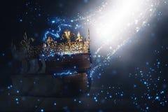 Imagem mágica de Mysteriousand da coroa e do livro velhos sobre o fundo preto gótico conceito medieval do período fotografia de stock royalty free
