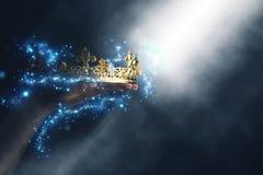 Imagem mágica de Mysteriousand da mão do ` s da mulher que guarda uma coroa do ouro foto de stock