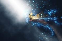 Imagem mágica de Mysteriousand da mão do ` s da mulher que guarda uma coroa do ouro imagem de stock