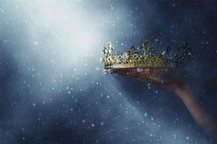 Imagem mágica de Mysteriousand da mão do ` s da mulher que guarda uma coroa do ouro sobre o fundo preto gótico conceito medieval  imagens de stock
