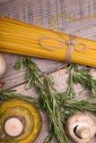 Imagem macro da massa, do cogumelo, de ovos de codorniz e de alecrins crus amarelos Ingredientes crus em uma tabela de madeira fotos de stock royalty free