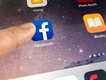 Imagem macro de um dedo aproximadamente para clicar o ícone de Facebook em uma tela do iPad Foto de Stock