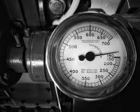 Imagem monocromática de um grande tacômetro velho do metal com um calibre redondo com o seletor marcado nos números montados em u imagens de stock