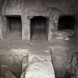 Imagem monocromática de um túmulo subterrâneo escuro com câmaras de enterro de conexão da ponte de pedra nos paphos Chipre imagens de stock