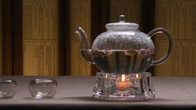 Imagem morna bonita da chaleira transparente do bule com chá preto verde saboroso em uma tabela com velas Chaleira de vidro imagens de stock royalty free