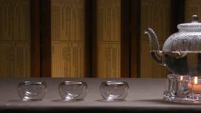 Imagem morna bonita da chaleira transparente do bule com chá preto verde saboroso em uma tabela com velas Chaleira de vidro imagem de stock