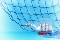 imagem náutica do conceito com o barco de vela na garrafa e na rede de pesca sobre a tabela e o fundo de madeira azuis Foco selet Fotos de Stock