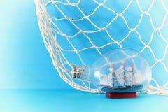 imagem náutica do conceito com o barco de vela na garrafa e na rede de pesca sobre a tabela e o fundo de madeira azuis Foco selet Imagens de Stock Royalty Free