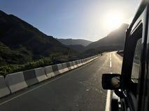A imagem na frente da cena do carro de esportes atrás como o sol que vai para baixo com as turbinas eólicas na parte traseira ilustração stock