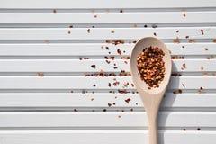 A imagem natural da fotografia do alimento de pimentões coloridos brilhantes lasca-se na colher de madeira nova e no fundo branco Fotos de Stock Royalty Free