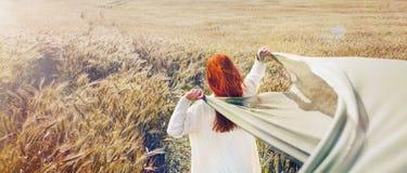 Imagem panorâmico da mulher vermelha de passeio do cabelo pelo campo liso Imagens de Stock Royalty Free