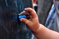 Imagem pequena do desenho da mão da menina no quadro-negro com giz azul imagem de stock royalty free