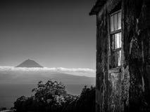 Imagem preto e branco da construção no primeiro plano e da montanha de Pico no fundo fotos de stock