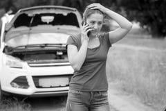 Imagem preto e branco da mulher triste que está em carro quebrado e em Ca Fotografia de Stock Royalty Free