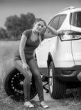 Imagem preto e branco da mulher triste que senta-se ao lado de carro quebrado em Fotos de Stock