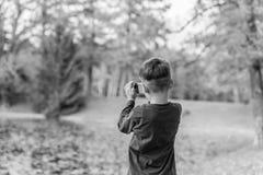 Imagem preto e branco de um rapaz pequeno que fotografa a natureza Imagens de Stock Royalty Free