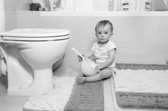 Imagem preto e branco do bebê adorável que senta-se no assoalho no bathr Imagens de Stock