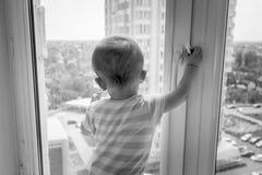 Imagem preto e branco do bebê que puxa o punho de janela e que tenta abri-lo Fotos de Stock Royalty Free