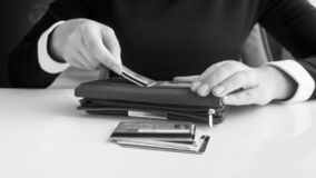 Imagem preto e branco do close up da mulher de negócios que põe cartões de crédito na carteira imagens de stock royalty free