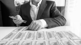 Imagem preto e branco do homem de negócios que senta-se atrás da mesa e que coloca o dinheiro nas fileiras imagem de stock royalty free