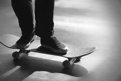 Imagem preto e branco dos pés de uma equitação do homem em seu skate imagens de stock royalty free