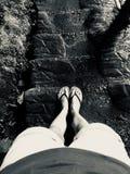 Imagem preto e branco dos pés fêmeas que estão em uma escadaria da rocha imagem de stock royalty free