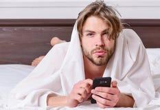 Imagem que mostra o homem novo que estica na cama Pés do homem que dormem na cama confortável Acorde a manhã fotos de stock royalty free