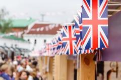 Imagem rasa do foco de um flack de Union Jack em uma fileira na estamenha da bandeira, acima de uma tenda do mercado Fotos de Stock Royalty Free
