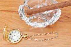 Imagem retro do relógio de bolso do ouro e de um charuto de Havana. Fotos de Stock