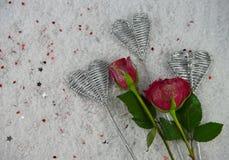 A imagem romântica da fotografia da estação do inverno do Natal ou do Valentim da rosa do vermelho floresce na neve com pétalas d Imagem de Stock Royalty Free