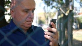 Imagem séria do homem que escreve a mensagem ao telefone celular atrás de uma cerca metálica vídeos de arquivo