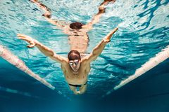 imagem subaquática do nadador novo no treinamento do tampão e dos óculos de proteção fotografia de stock royalty free