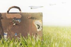Imagem surreal dos aviões de papel que voam sobre uma mala de viagem imagens de stock