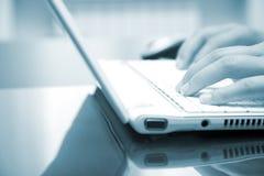 Imagem tonificada azul da mão fêmea que datilografa em um PC Imagens de Stock