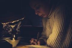 Imagem tonificada da menina da escrita e do gato preto e branco sob a lâmpada Imagens de Stock Royalty Free